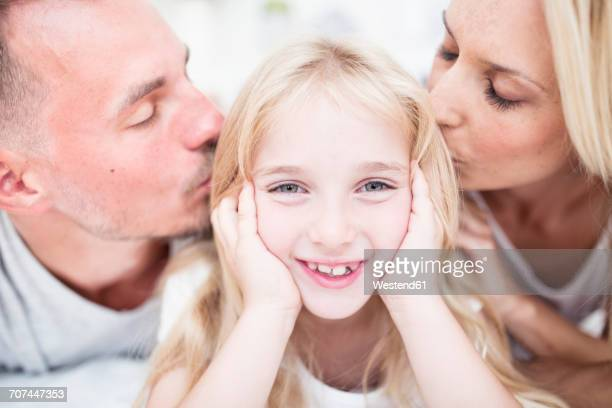 Portait of smiling girl being kissed by parents