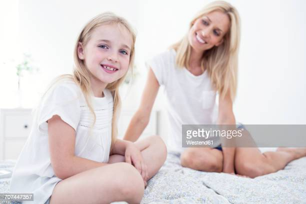 Portait of smiling girl sitting on bed with mother