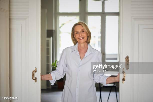 portait of smiling mature woman opening door at home - open blouse - fotografias e filmes do acervo