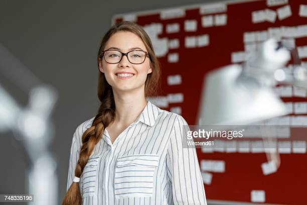 Portait of smiling young woman in office in front of scrum board