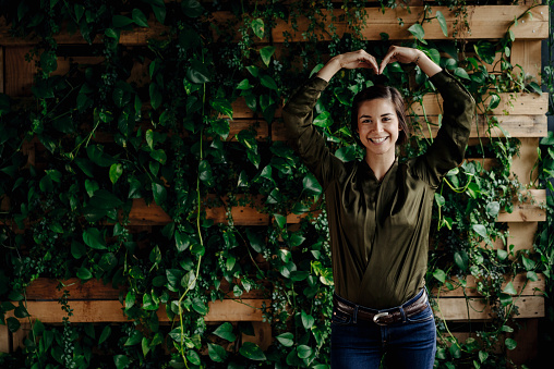Portait of smiling young woman shaping heart at wall with climbing plants - gettyimageskorea