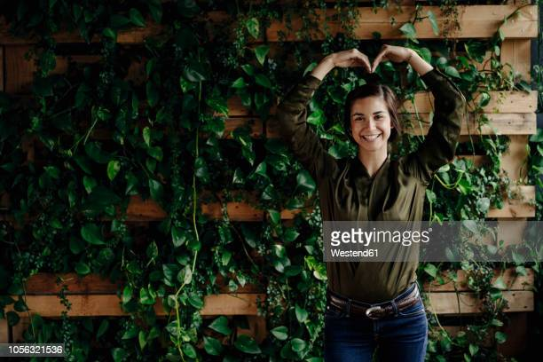portait of smiling young woman shaping heart at wall with climbing plants - gesturing stock pictures, royalty-free photos & images