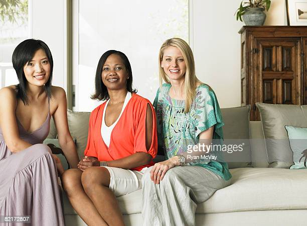 Portait of three women sitting on sofa