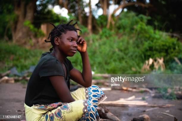 portait of young african woman sitting on the ground - malawi stock pictures, royalty-free photos & images
