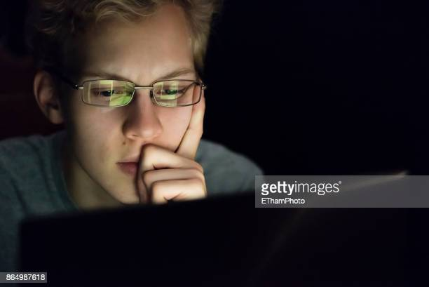 Portait of young hacker with computer screen reflecting in the man's glasses.