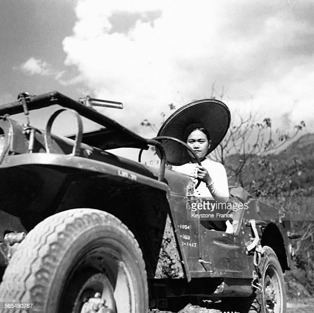 Portant un large chapeau de paille une jeune fille assise dans un véhicule toutterrain dans la région du Lai Châu au Viêt Nam circa 1950