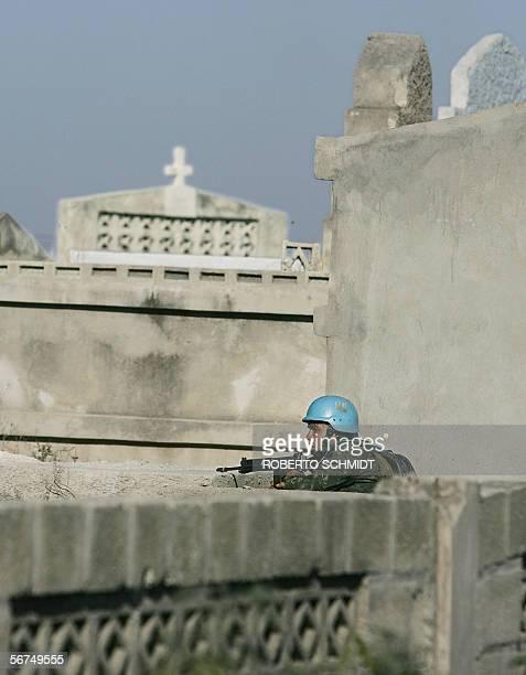Port-au-Prince, HAITI: A Brazilian UN peacekeeper takes a position behind a tomb in the Drouillard cemetary in Port-Au-Prince, Haiti 04 February as...