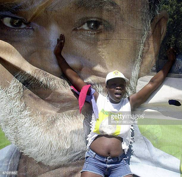 A supporter dances in front of a poster of Haitian Presidentelect Rene Preval 08 March in southern PortauPrince while the newly elected president...