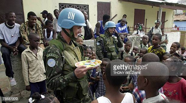 A UN peacekeeper hand out candy to Haitian school children 09 March 2007 in the St Martin area of PortauPrince The children celebrated the end to the...