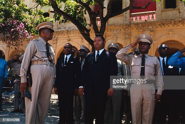 President Jean Claude Duvalier named chief executive after death of his father Papa Doc reviews Army troops here He is escorted by General Garcia...