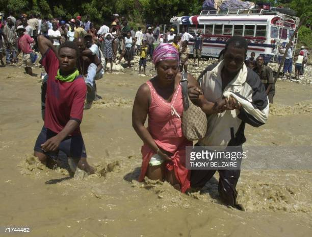 Residents walk across a floodswollen river 29 August 2006 after the collapse of a bridge in Grand Goave 54 km south of PortauPrince following...