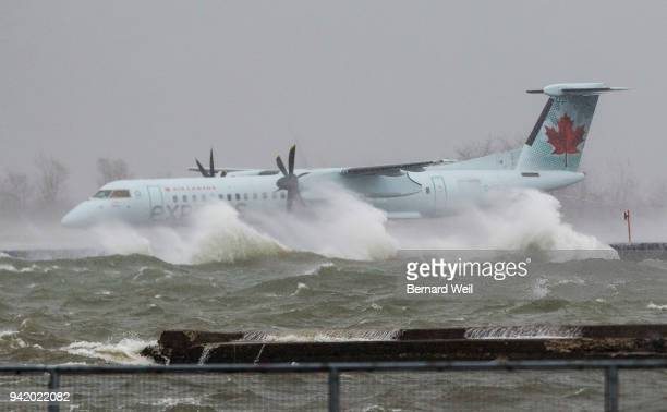 Porter Airlines plane taxis at Billy Bishop Airport Toronto as high winds sweep through the GTA churning the waters of Lake Ontario at the edge of...