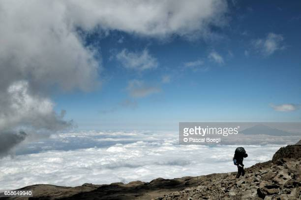 Porter and clouds at Barafu camp with Mount Meru in the distance, Kilimanjaro National Park