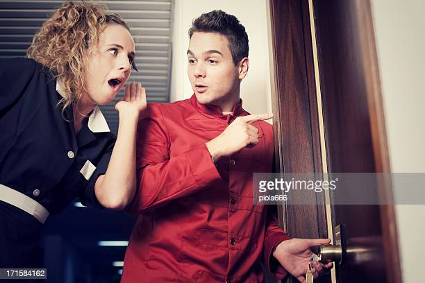 Porter and hotel maid eavesdropping at the door