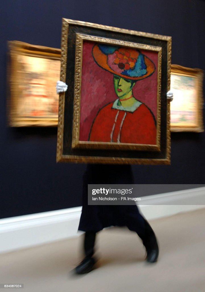 A porter at Sotheby's London auction house moves a portrait