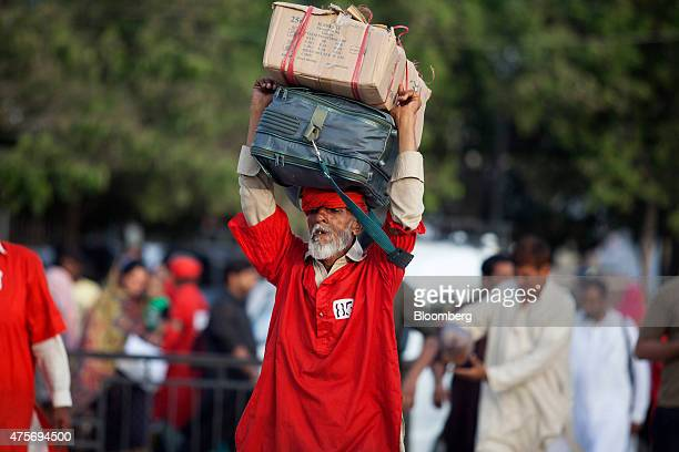 A porter carries a passenger's luggage on his head at Karachi Cantonment railway station in Karachi Pakistan on Friday May 29 2015 Pakistan's budget...