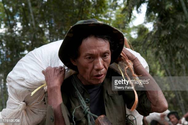 A porter carrying supplies for a team of the relief group Free Burma Rangers walks through a forest on his way to a displaced people community in...
