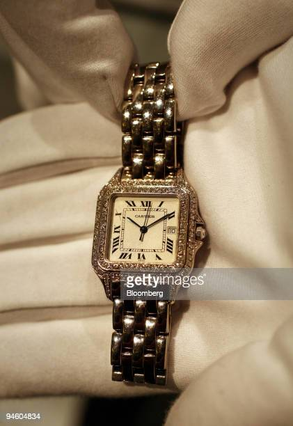 A porter displays a Cartier 18K white gold and diamond 'Panthere' wristwatch belonging to Cher worth an estimated $50007 at Sotheby's in central...