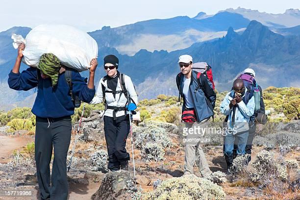 Porter, guide and tourists climbing Mount Kilimanjaro, Tanzania