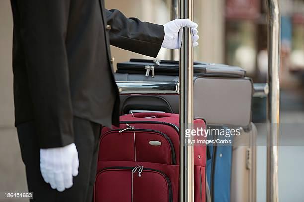 Porter holding luggage cart