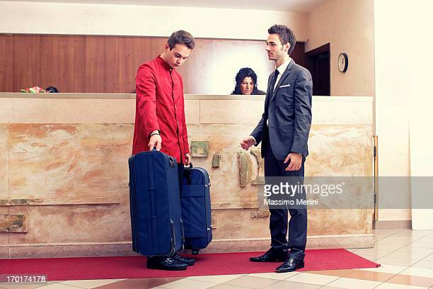 Porter invite businessman to follow at the  room,