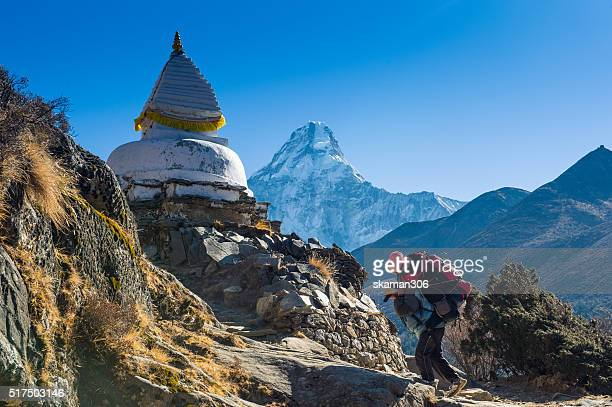 porter man carry bag move up to stupa with ama dablam mountain background