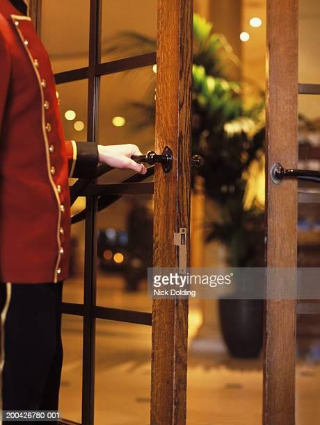 Porter opening door, side view