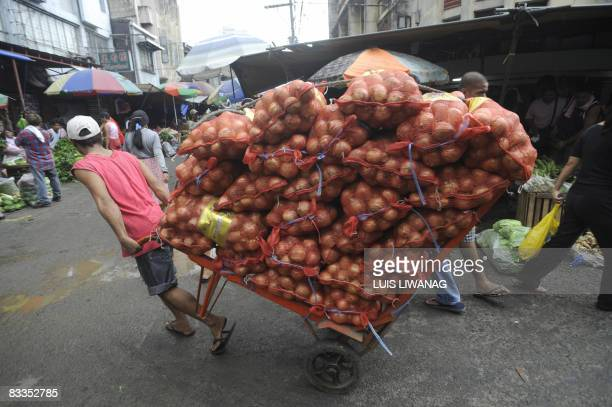 A porter pull an onion laden cart for delivery to the Divisoria market in Manila on October 20 2008 Rising cost of fuel and basic commodities are...