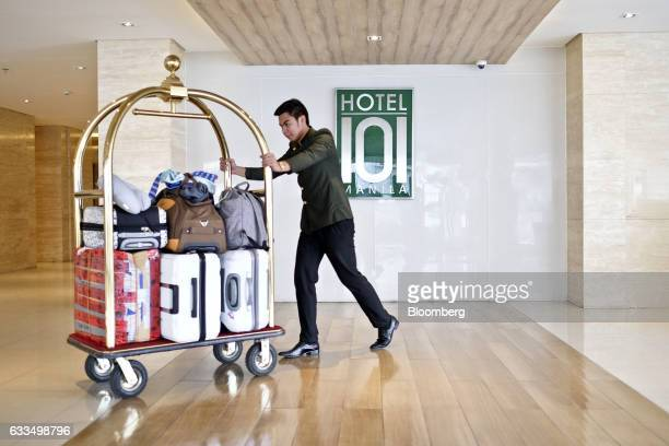Porter pushes a trolley laden with luggage at a Hotel of Asia Inc. Hotel 101 property, operated by DoubleDragon Properties Corp., in Manila, the...