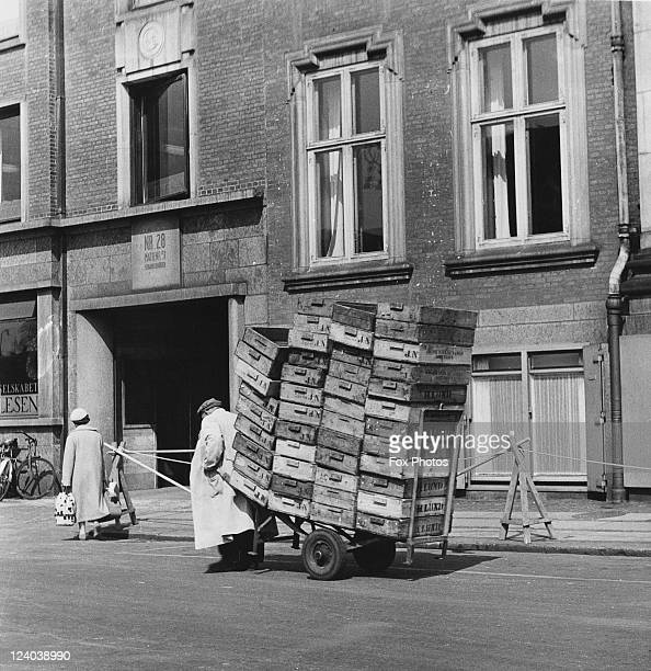 A porter removes empty crates from the fish market in Gammel Strand Copenhagen Denmark in the early morning 1957