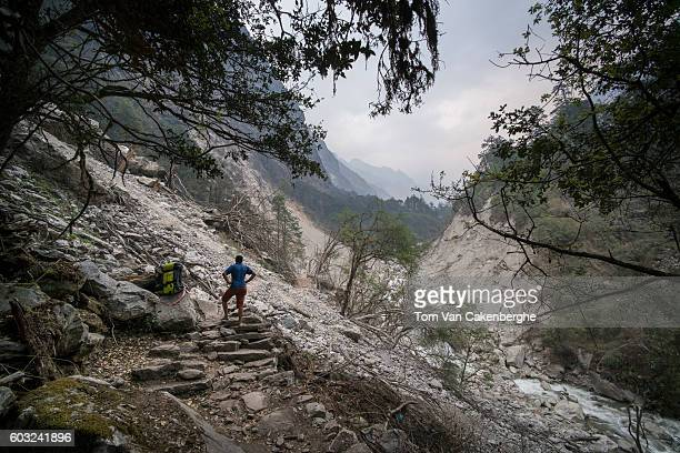 A porter stands in front of an enormous landslide that damaged the popular Langtang Valley trekking trail during the 2015 Gorkha earthquake On April...
