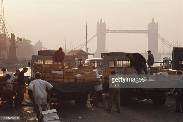 Porters and traders at Billingsgate fish market unload boxes of their goods to make ready for sale London circa 1970 In the background is Tower...