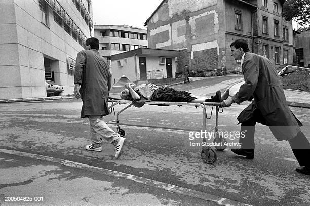 Porters from Kosovo Hospital rush a man wounded by a shell to the emergency room. During the 47 months between the spring of 1992 and February 1996,...