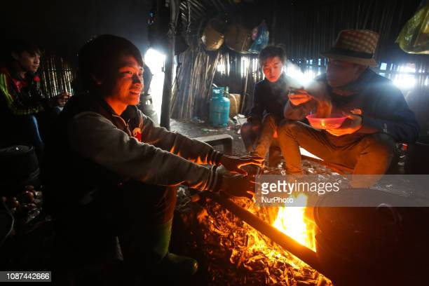 Porters in a self made hut warming up and eating they are carrying parts for the new cable car Fansipan mountain in Vietnam with the highest peak...