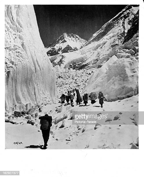 Porters on the way to base camp on the Khumba glacier move up the 'trough' between large ice pinnacles near Mount Everest 1953