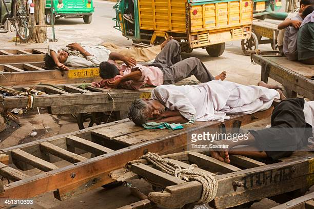 Porters sleeping on their carts in Old Delhi. Other keywords: lying, resting, sleeping, human powered, transport, cargo, freight, people, men,...