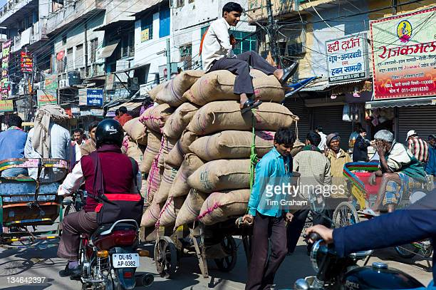 Porters with sacks of dates at Khari Baoli spice and dried foods market Old Delhi India