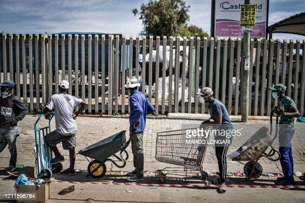 Porters with wheelbarrows and carts queue to help residents of the Olievenhoutbosch township in Centurion, carry their food parcels on May 2, 2020...