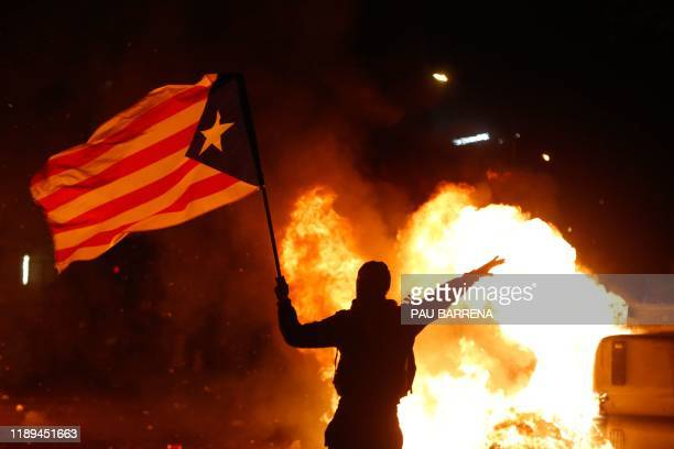 TOPSHOT A portester waves a Catalan proindependence Estelada flag next to garbage containers burning during a protest called by the Catalan...