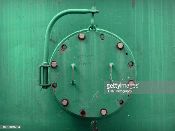 porthole of rusty industrial tank - old frigate stock photos and pictures