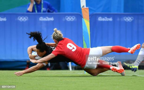 Portia Woodman of New Zealand dives over for a try under pressure from Natasha Hunt of Great Britain during the Women's Rugby Sevens Semi Final match...