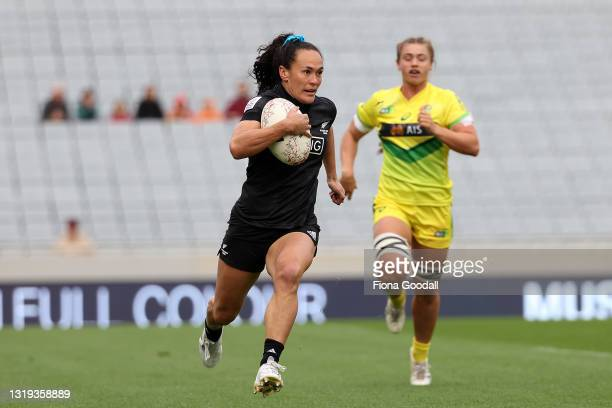 Portia Woodman of the Black Ferns Sevens runs in to score a try defended by Evania Pelite of the Australian Sevens at Eden Park on May 22, 2021 in...