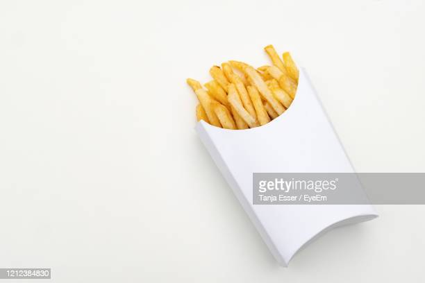 a portion french fries in a white cardboard box. white paper background and packaging - fast food french fries stock pictures, royalty-free photos & images