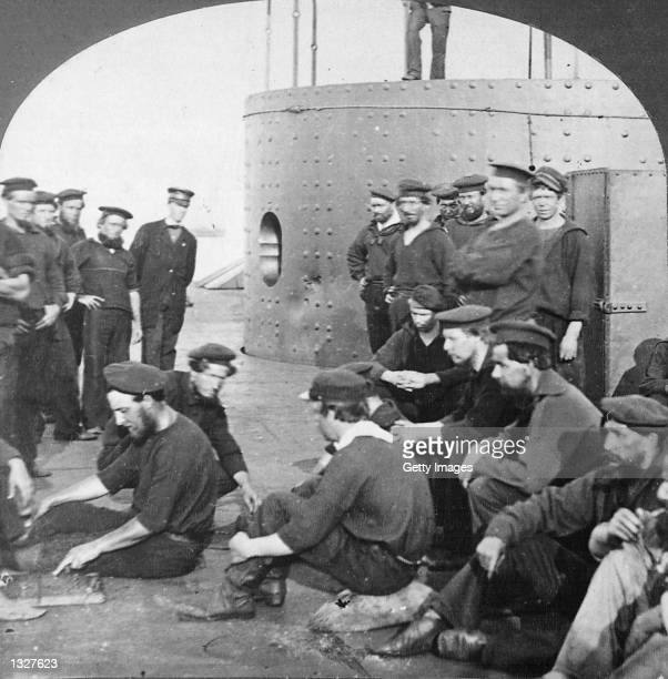 A portion of the crew of the Federal ironclad warship the USS Monitor are photographed on the deck of the Civil War ship The steam engine from the...