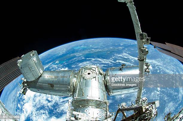 A portion of the International Space Station backdropped by Earths horizon.