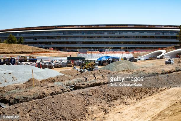 A portion of the main building is visible above a construction site and two partially completed tunnels at the Apple Park known colloquially as 'The...