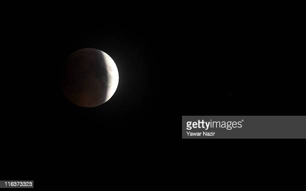 A portion of the moon crosses into the Earth's shadow on June 16 2011 in Srinagar the summer capital of Indian Administered Kashmir Astronomers in...