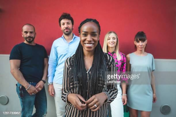 portirat of a 30s woman looking at camera with a group of friends behind her - anti racism stock pictures, royalty-free photos & images