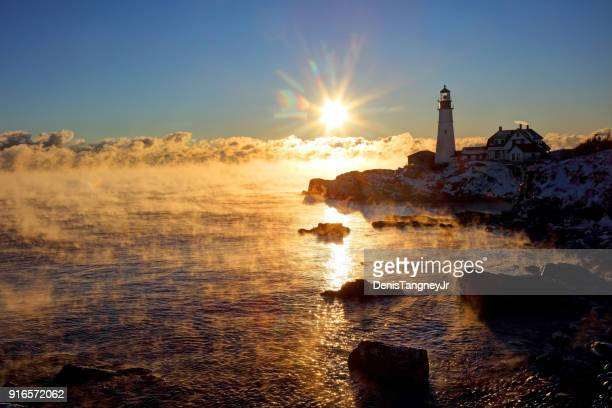 portland head lighthouse in arctic sea smoke - portland maine stock photos and pictures