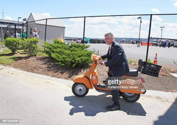 Portland mayor Ethan Strimling hops on his scooter after greeting dignitaries from Nova Scotia after they disembarked The Cat following its arrival...